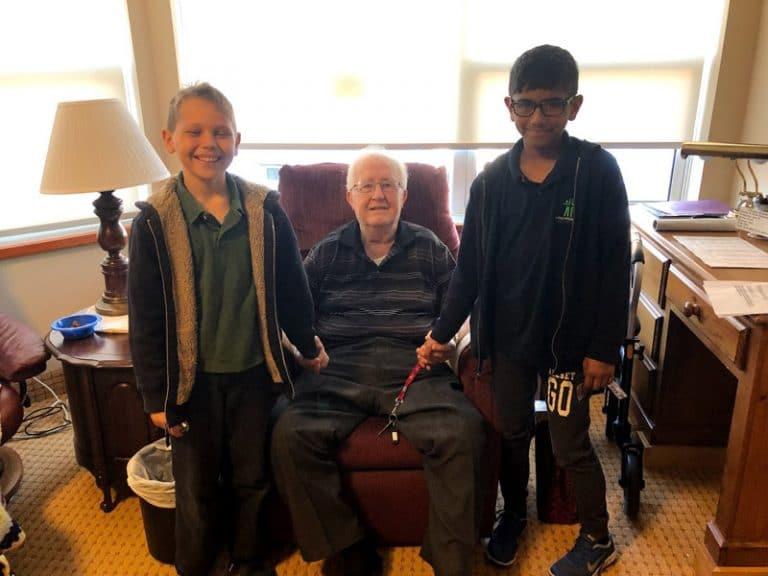 Foundation boys with elderly man in nursing home